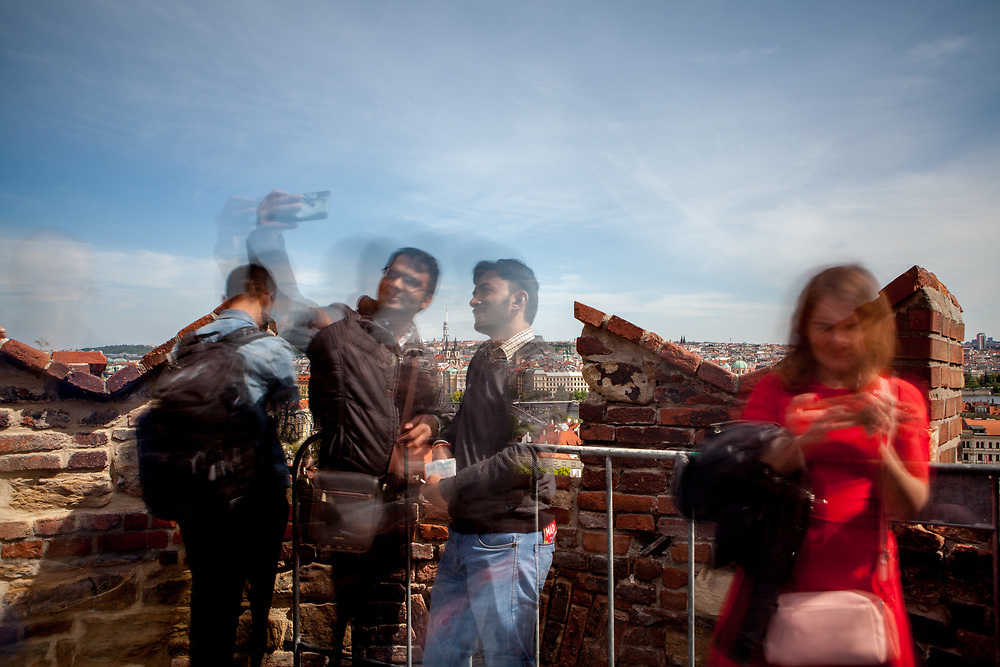 Tourists photographing and doing selfies at  Prague Castle at an panoramic viewpoint showing the cityscape of Prague from above.