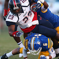 Baldwyn's Corion Doss is tripped up by Booneville's Camron Young during Friday night's Skunk Bowl game against Baldwyn.