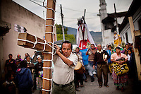 A man carries a wooden cross during a Semana Santa procession in the highlands of Uspantan, Guatemala, on March 30, 2012. This area suffered heavy violence against the residents during the civil war, where the military publicly executed possible guerrillas in the plaza.
