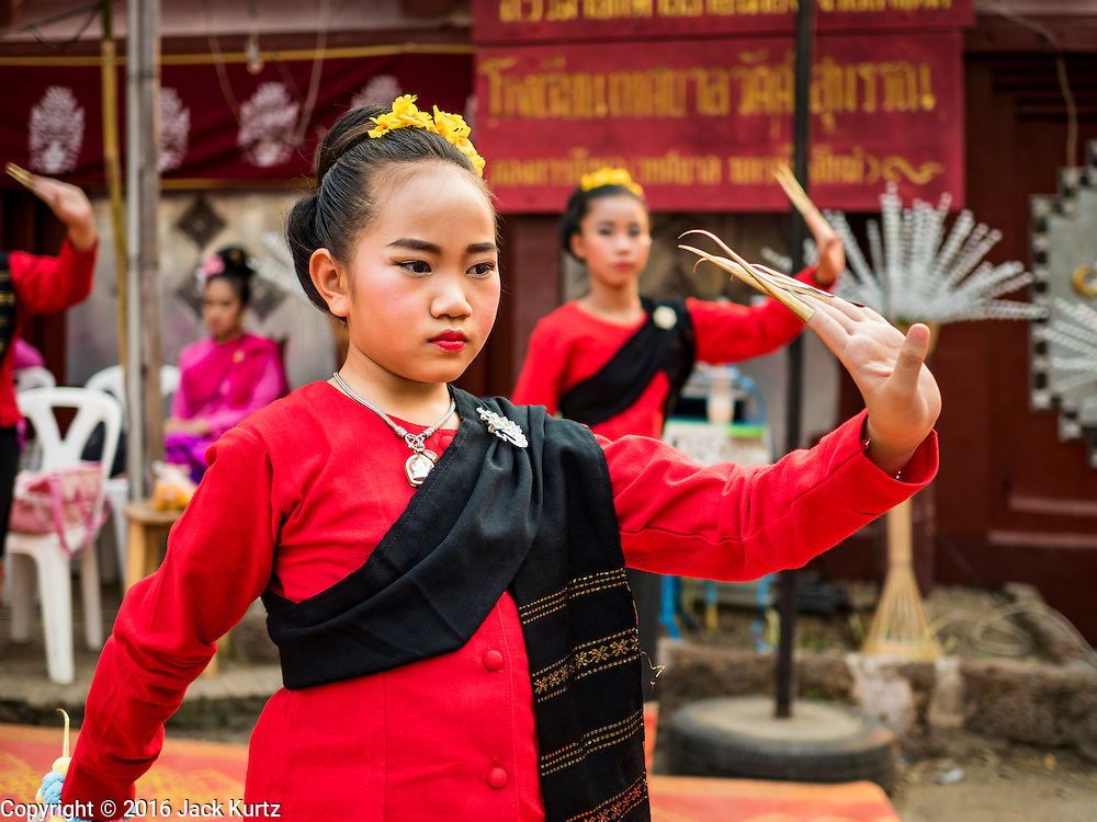 """03 APRIL 2016 - CHIANG MAI, THAILAND: Thai girls perform a traditional northern Thai dance at the dedication of the ubosot, or ordination hall, at Wat Sri Suphan. Wat Sri Suphan is also known as the """"Silver Temple"""" because of its silver ubosot, or ordination hall. The temple is more than 500 years old but the silver ordination hall was recently remodeled. The ordination hall is covered in silver and the interior is completely done in silver and gold. It's traditionally served as the main temple for the silversmiths of Chiang Mai, whose community is around the temple.     PHOTO BY JACK KURTZ"""