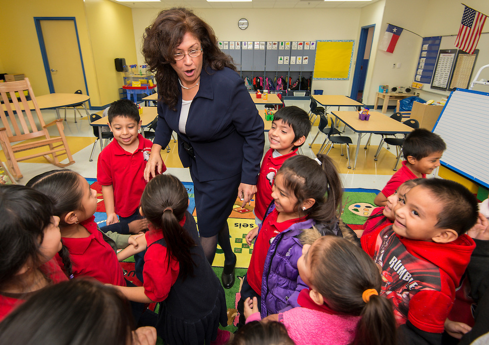 Principal Amelia Cardenas-Aguilar greets kindergarten students on the first first day of class at the new Sherman Elementary School on Monday.