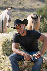 Hot black cowboy with an open shirt holding a saddle on a dirt road good looking black cowboy on hay bales by horses