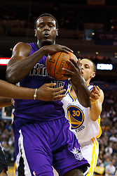 April 10, 2011; Oakland, CA, USA;  Sacramento Kings center Samuel Dalembert (10) grabs a rebound in front of Golden State Warriors point guard Stephen Curry (back) during the first quarter at Oracle Arena.