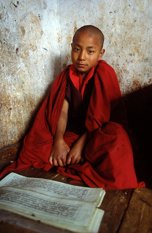 A novice monk during prayer studies at Semtokha Monastery near Thimphu.