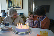 Family, young child and elderly Aunt prepare to blow out birthday candles as grandmother holds 3-year old child.