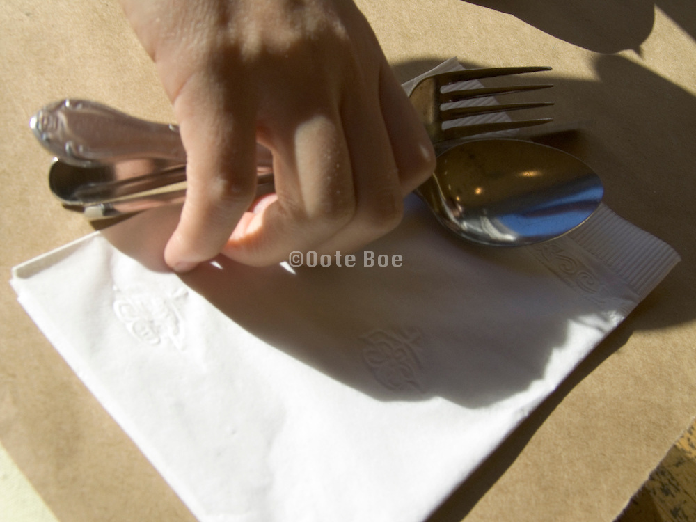 a hand placing fork spoon and knife on the table