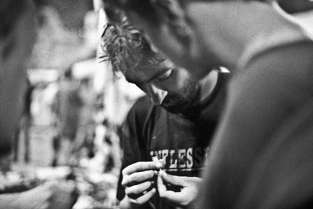 Genova, venerdì 20 luglio 2001. Giornata delle piazze tematiche.  Dopo il corteo della disobbedienza civile negli interventi dal palco allo stadio Carlini vengono denunciate le violenze subite da parte delle forze di polizia..Alcuni manifestanti denunciano di essere stati sfiorati da spari ad altezza uomo. Qualcuno ha raccolto dei bossoli, che passano di mano in mano per essere osservati dai manifestanti.