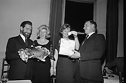 Irish Shell Christmas Party..1964..16.12.1964..12.16.1964..16th December 1964..the staff at Irish Shell Ltd held their annual Christmas party at The Salthill Hotel, Monkstown...Image shows Kevin Hayes and his girlfriend Eileen McDonnell after they won a ham in the prize draw. Included in the picture are Matt Feddis ,Sec Social Club and Margot mcKenna as they continue the draw. Kevin popped the question to Eileen at the party and she accepted...