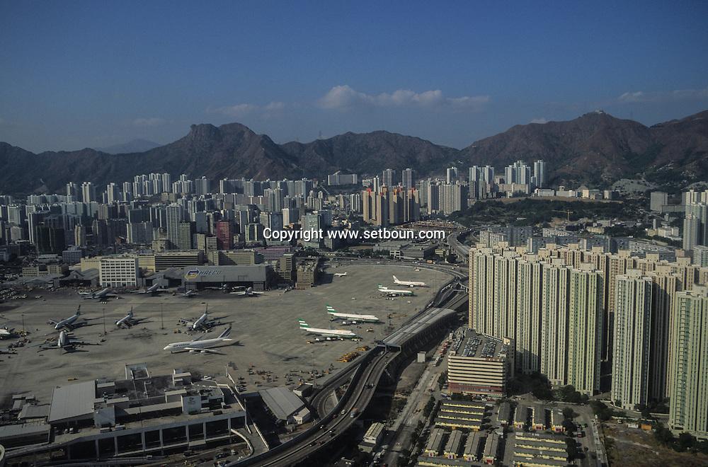Hong Kong. planes landing on THE OLD Kai Tak airport in the CENTER OF THE city. THE AIRFIELD IS BUILD ON A RECLAIMED LAND       / avion  atterissant au dessus de la mer et la ville, sur l'aeroport de Kai Tak, . La piste d'atterissage est construite sur un polder, juste devant  Mongkok, le quartier le plus dense de la planète       premier Airbus A 340 livres a Cathay pacific  / R82/    L1086  /  R00082  /  p0006040