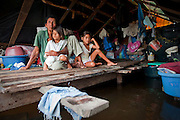 Guillermo Huarata Pairo Genayo sits with his 2 young girls, the only 2 that have survived of his wife's 15 children. Guillermo supports his family by fishing and performing various other odd jobs. Image © Jonah Markowitz/Falcon Photo Agency