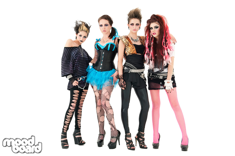 Portrait of all female rock band posing together over white background