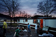 The Goins family attempts to move belongings into a new trailer as dusk settles over Chauncey, Ohio on March 11, 2006. The Goins family was displaced for a time after a drunk driver swerved off the road and crashed into their trailer. Communities that once struggled to get by can no longer make ends meet after the economic downturn in the United States.