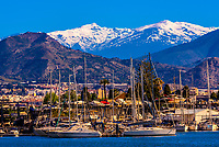 Sailboats in the harbor of Motril, on the Costa Tropical of Granada Province, with the snow capped Sierra Nevada Mountains in the background, Andalusia, Spain.