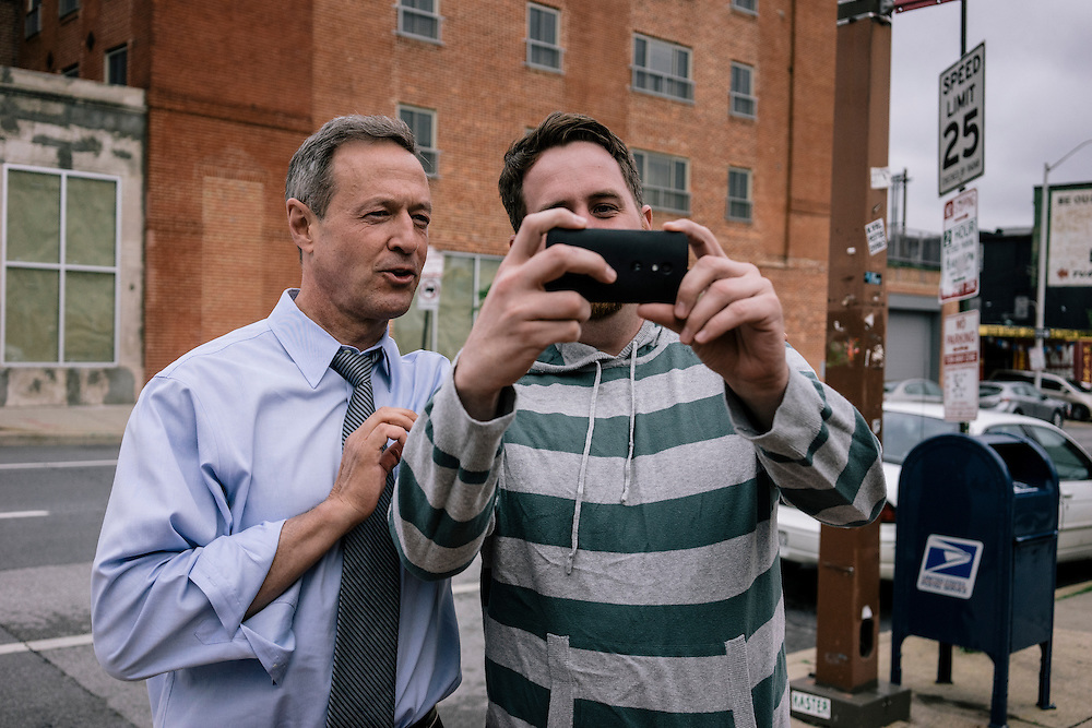 Former Maryland Governor Martin O'Malley takes a selfie with Baltimore residents Clark Miller and Kendra Hay on Thursday, May 21, 2015. O'Malley is considering a run for President of the United States.