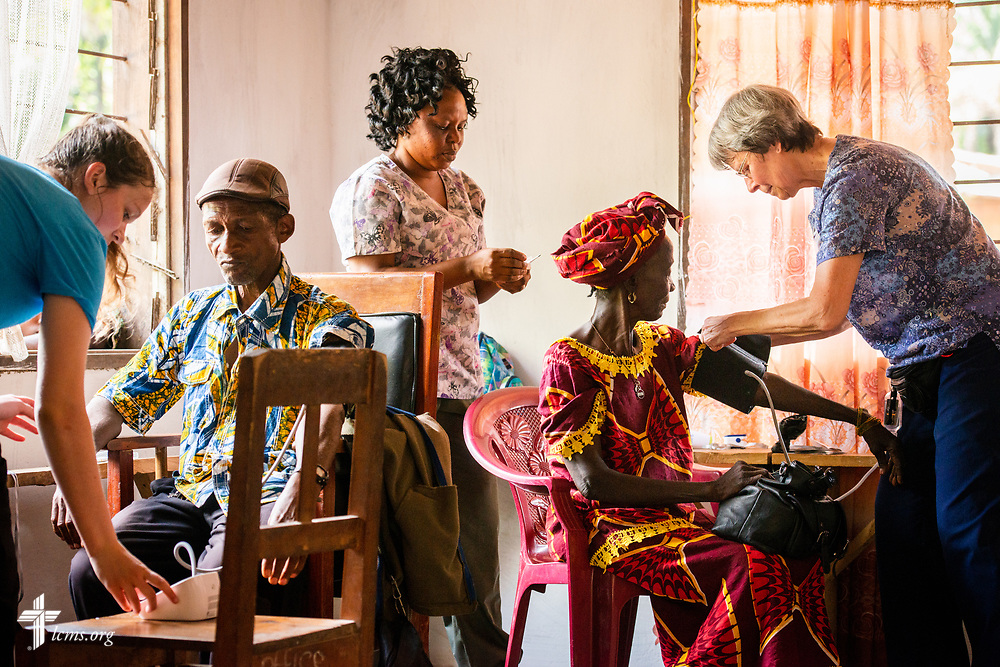 Team members Hayden Rensner, a student at Concordia University, Nebraska, and Bonnie Hartman, a member of Faith Lutheran Church, Godfrey, Ill., works with counterpart nurses from Sierra Leone as they prepare vitals for patients on the first day of the LCMS Mercy Medical Team on Monday, May 7, 2018, in the Yardu village outside Koidu, Sierra Leone, West Africa. LCMS Communications/Erik M. Lunsford