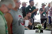 """Elliot Strunk, center, and other members of the Ohio University alumni community applaud a performance by the Ohio Alumni Varsity Band at a barbecue on the College Green on May 31, 2014. The event, for Ohio University alumni and their families, was part of the """"On The Green"""" weekend, which was hosted by the Ohio University Alumni Association. Photo by Lauren Pond"""