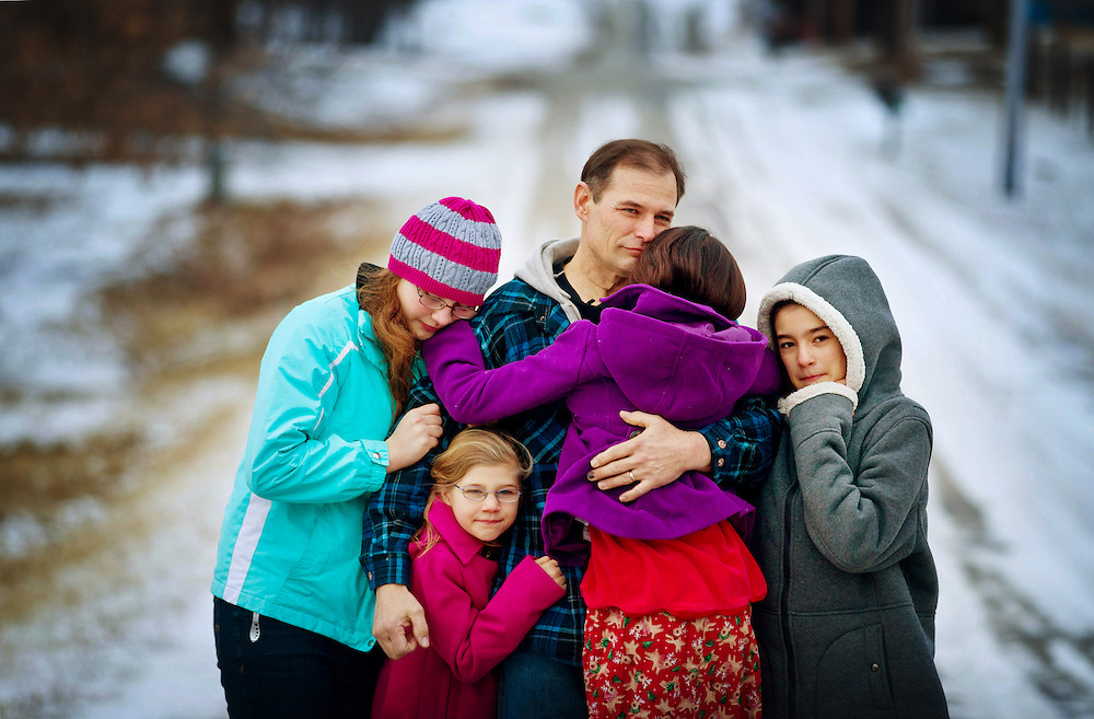 "Iowa National Guard Spc. John Kerschner, 46, hugs four of his daughters including, from left, Grace, 14, Gianna, 7, Gaela, 9, and Gladys, 11, outside of their home in Clearfield, Iowa. Kerschner served at Combat Outpost Dand Patan with Bravo Company of the 1-168th battalion of the Iowa National Guard. ""I don't want to say it was an enjoyable experience"" in Afghanistan, Kerschner said. ""But it was a worthwhile one."" 