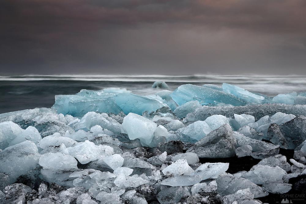 Piles of icebergs on Jökulsárlón beach in south-east Iceland, at dusk.