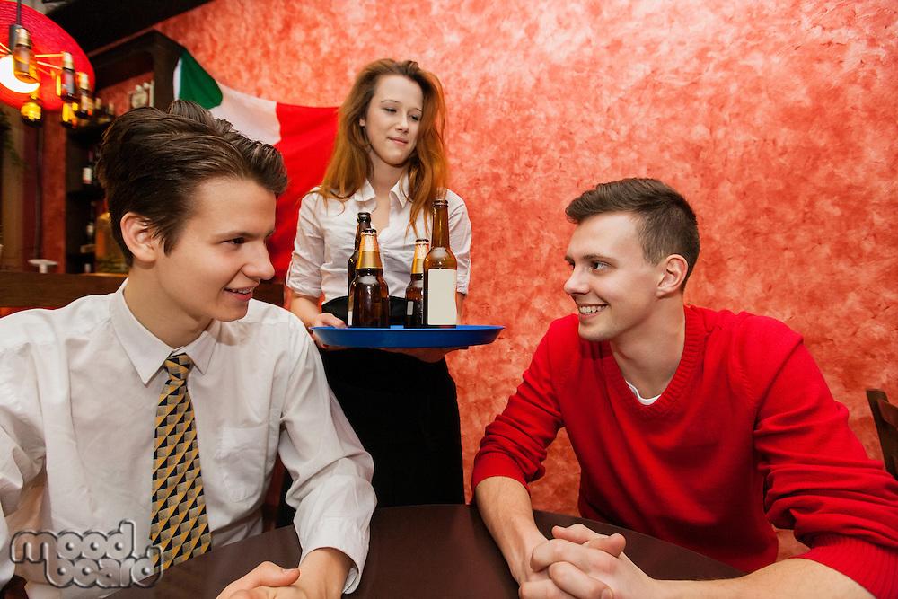 Waitress serving drinks to men in restaurant