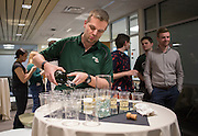 Marco Habermann, an assistant professor in the College of Business, pours champagne at the beginning of the recption after a day of training with Sogeti on March 10, 2016. Photo by Emily Matthews