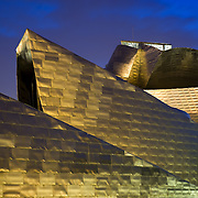 Guggenheim Museum in Bilbao at dusk. It was designed by Frank O Gehry, and the main materials used for the building are titanium, glass and limestone.