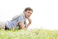 Portrait of young man lying on grass against clear sky