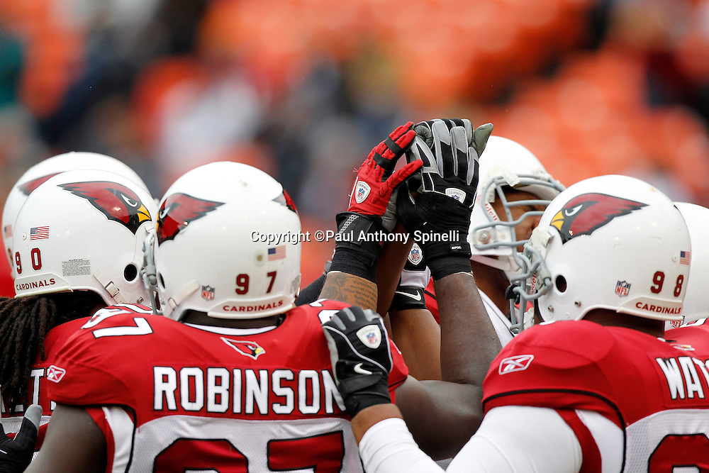 A group of Arizona Cardinals players join hands before the NFL week 17 football game against the San Francisco 49ers on Sunday, January 2, 2011 in San Francisco, California. The 49ers won the game 38-7. (©Paul Anthony Spinelli)
