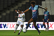 Milton Keynes Dons striker Dylan Asonganyi (37) takes a shot at goal under pressure from Wycombe Wanderers defender Sido Jambati (2) during the EFL Trophy match between Milton Keynes Dons and Wycombe Wanderers at stadium:mk, Milton Keynes, England on 12 November 2019.