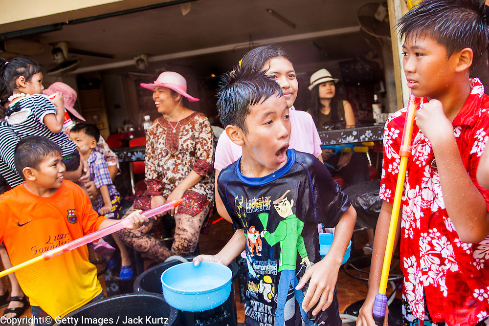 14 APRIL 2013 - BANGKOK, THAILAND:  Boys in a water fight on Soi Nana on April 14, 2013 in Bangkok, Thailand. The Songkran festival is celebrated in Thailand as the traditional New Year's Day from 13 to 15 April. The throwing of water originated as a way to pay respect to people and is meant as a symbol of washing all of the bad away. PHOTO BY JACK KURTZ