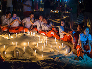 26 DECEMBER 2014 - PATONG, PHUKET, THAILAND: Thai students pose with the candles they lit for victims of the 2004 tsunami on Patong Beach in Patong, Phuket. Hundreds of people died in Patong and nearly 5400 people died on Thailand's Andaman during the 2004 Indian Ocean Tsunami that was spawned by an undersea earthquake off the Indonesian coast on Dec 26, 2004. In Thailand, many of the dead were tourists from Europe. More than 250,000 people were killed throughout the region, from Thailand to Kenya. There are memorial services across the Thai Andaman coast this weekend.    PHOTO BY JACK KURTZ