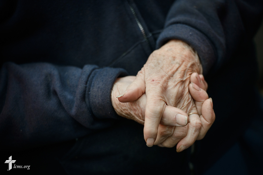 Mini Kessinger, an 88 year-old flood victim and parishioner, folds her hands during a prayer on Saturday, Jan. 9, 2016, in Watseka, Ill. A flood at the end of December ravaged over a 60-block radius of the town. LCMS Communications/Erik M. Lunsford