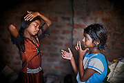 Jyoti, 10, (left) and her younger sister Poonam, 9, (right) are oiling their hair while getting ready for school, inside their newly built home in Oriya Basti, one of the water-contaminated colonies in Bhopal, central India, near the abandoned Union Carbide (now DOW Chemical) industrial complex, site of the infamous '1984 Gas Disaster'.