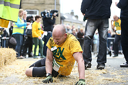 © Licensed to London News Pictures. 17/04/2017. Gawthorpe UK. A competitor breaks down at the finish line of the mens race of The World Coal Carrying Championships in the village of Gawthorpe in Yorkshire. Every year Men & women carry huge sacks of coal from the Royal Oak Pub in Ossett 1012 metres to the finish line at the Maypole Green in the village of Gawthorpe. Photo credit: Andrew McCaren/LNP