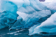 Blue ice of a glacier in Antarctica. The ice of blue icebergs contains fewer air bubbles than those appearing more or less white. On rainy days their colour appears particularly intense.