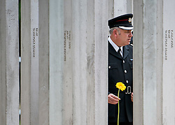© Licensed to London News Pictures. 07/07/2015. London, UK. A police officer laying a flower at the memorial following the service. A memorial service in Hyde Park London on the 10th anniversary of the 7/7 bombings in London. The event is attended by Prince William, survivors of the attack and family of those who lost their lives. Photo credit: Ben Cawthra/LNP