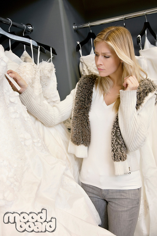 Young woman looking at price tag of bridal gown in boutique