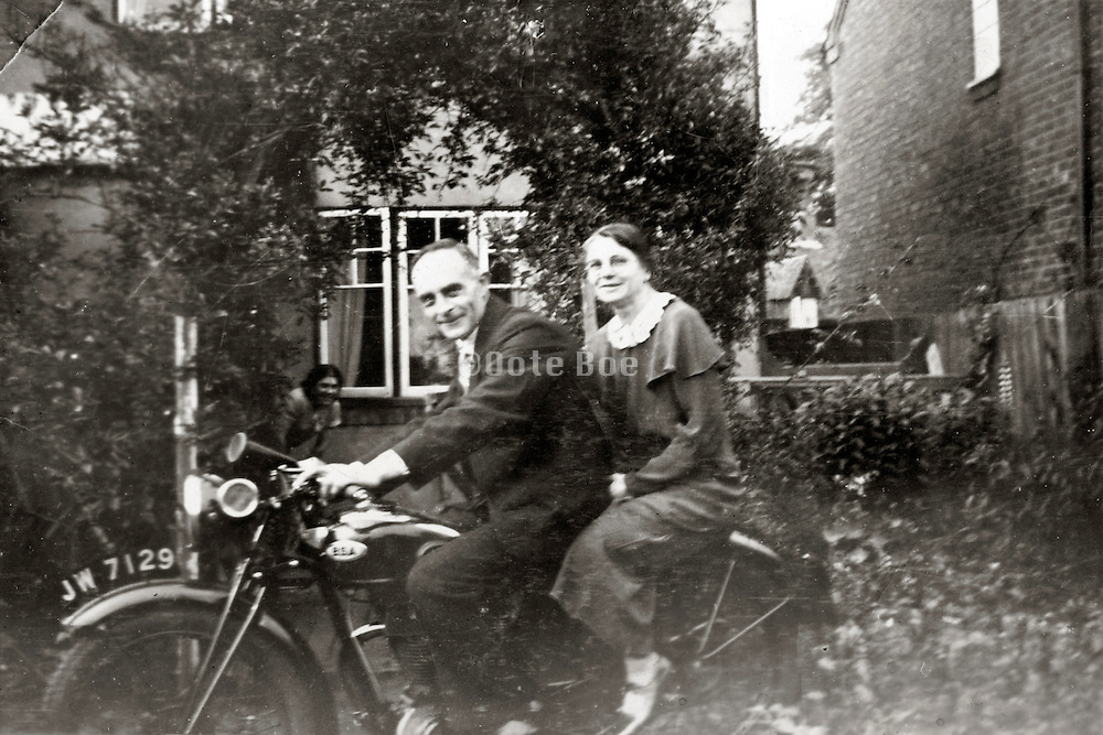 elderly couple in front of a house sitting on a motorcycle