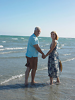 Senior couple walking on tropical beach back view