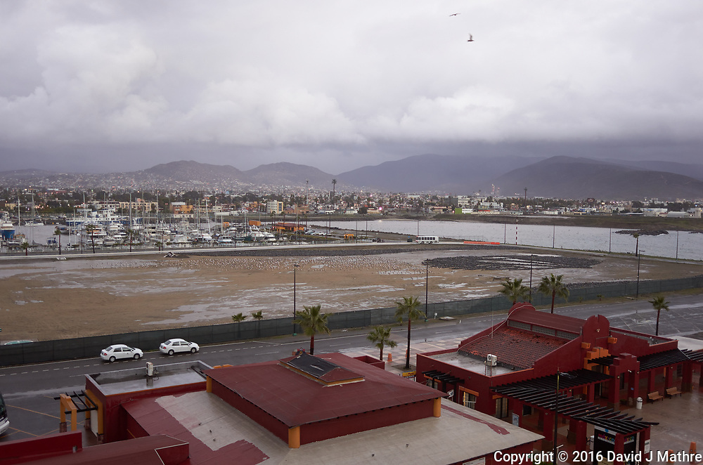 "(Image six of nine) Panorama of the Ensenada harbor in Mexico on a grey and raining day from the deck of the MV World Odyssey. The other cruse ship is the Carnival Imagination. Once all of the students, faculty, staff, and life long learners were aboard we would be ready to begin the 102 day ""round the world"" Semester at Sea Spring 2016 Voyage. Composite of nine images taken with a Leica T camera and 23 mm f/2 lens (ISO 250, 23 mm, f/2, 1/80 sec). Panorama stitched using AutoPano Giga Pro."