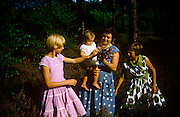 A mother and two teenage girls stand among heather in country field during summer time in the early 1960s. Standing in the naturally-growing heather in afternoon sunshine, the women and the young child are looking at the plants that they've just picked to show the youngster. Polka dots seem to be the fashion in this picture recorded on a film camera by the child's father, an amateur photographer in 1960. The picture shows us a memory of nostalgia in an era from the last century.
