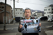 """Kamaishi, Japan - <br /> <br /> Japan 4 Years Later<br /> <br /> On March 11, 2011, a magnitude 9 earthquake struck in the Pacific Ocean about 20 miles off of the Northeastern Japanese coast of Honshu and produced a series of waves, or tsunamis, that reached 30 feet or higher. These waves slammed into a protective seawall built by the Japanese government at an estimated cost of $1.6 billion. The seawalls failed.<br /> <br /> Along the coast, more than 15,000 people lost their lives. 230,000 either lost their homes or were displaced. About 87,000 still live in temporary housing four years later.<br /> <br /> In the temporary housing near Kamaishi, Japan, about half the former residents are gone now. The Japanese government has offered subsidies of $40,000 to $60,000 to help rebuild homes that now cost $300,000 to $450,000 to rebuild, due to the shortage of construction workers and the cost of building materials. Some have moved in with relatives; others moved into permanent apartments and manyhave simply left the area for good.<br /> <br /> Tokyo has set aside $155 billion to rebuild, and yet many in Kamaishi wonder where the money is going. Some of it is spent on schemes to literally raise the ground up to 15 feet in devastated towns like Otsuchi and Rikuzentakata City, which were practically flattened by the tsunami. Even more is being spent to repair the failed seawall.<br /> <br /> Despite efforts by Tokyo to raise the ground level and repair the sea walls, many people in the area are losing hope of having their lives back. Takemi Wada, who lost her home and mother at Rikuzentakata City, said she'll never move back even with the elevated land. """"Who wants to live on top of a graveyard?"""" she asked.<br /> <br /> Photo shows: SHINPEI KIKUCHI, a photographer living in Kamaishi, holds a photo he shot from the spot he is standing of the oncoming water from the tsunami of 2011. The tsunami claimed more than 1,100 people from the city of Kamaishi. <br /> ©Earnie Grafton/E"""
