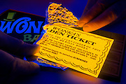 A Golden ticket is exposed by a pair of hands that unwraps a Wonka candy bar.Black light