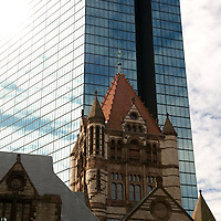 """The building's plan is a modified Greek Cross with four arms extending outwards from the central tower, which stands 64 m (211 ft) tall. The church is situated in Copley Square, in the shadow of the John Hancock Tower. Having been built in Boston's Back Bay, which was originally a mud flat, Trinity rests on some 4500 wooden piles, each driven through 30 feet of gravel fill, silt, and clay, and constantly wetted by the water table of the Back Bay so they do not rot if exposed to air..Its interior murals, which cover over 21,500 square feet (about 2,000 m²) were completed entirely by American artists. Richardson and Brooks decided that a richly colored interior was essential and turned to John La Farge (1835–1910) for help. La Farge had never performed a commission on this scale, but realized its importance and asked only for his costs to be covered. The results established La Farge's reputation..The church's windows were originally clear glass at consecration in 1877, with one exception, but soon major windows were added. Four windows were designed by Edward Burne-Jones and executed by William Morris. Another four windows were exceptional commissions by John La Farge, and revolutionized window glass with their layering of opalescent glass..Trinity Church is the only church in the United States and the only building in Boston that has been honored as one of the """"Ten Most Significant Buildings in the United States"""" by the American Institute of Architects (AIA). In 1885, architects voted Trinity Church as the most important building in the U.S.; Trinity Church is the only building from the original 1885 list still included in the AIA's current top ten list. The building was designated a National Historic Landmark on December 30, 1970..The church also houses sculptures by Daniel Chester French and Augustus Saint-Gaudens.Wikipedia"""