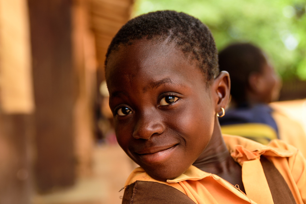 School child smiling in front of the camera, Accra, Ghana.