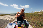 Young woman eats on picnic mat on the ground near a deserted road