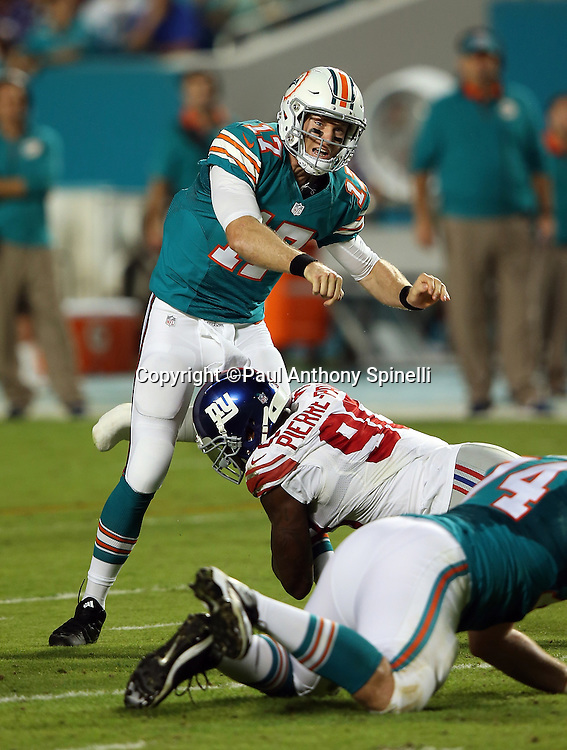 Miami Dolphins quarterback Ryan Tannehill (17) throws a pass as he gets hit by New York Giants defensive end Jason Pierre-Paul (90) with his right arm covered in a cast caused by a non-football injury during the NFL week 14 regular season football game against the New York Giants on Monday, Dec. 14, 2015 in Miami Gardens, Fla. The Giants won the game 31-24. (©Paul Anthony Spinelli)