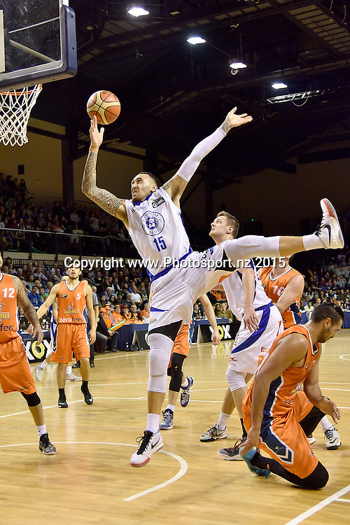 Leon Henry of the Saints jumps to shoot as he falls over Tai Wesley of the Southland Sharks during the NBL final basketball match between Wellington Saints and Southland Sharks at the TSB Arena in Wellington on Sunday the 5th of July 2015. Copyright photo by Marty Melville / www.Photosport.nz