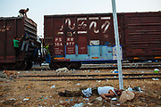 A man is lying down beside the railroad waiting for the train departure in the station of Arriaga, Mexico, April 21, 2013.