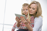 Woman using digital tablet with daughter at home