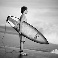Young surfer boy standing on the beach in Costa Rica and staring at the big waves